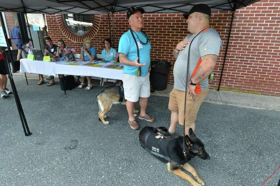 Veterans Ray Benkosky with service dog Pearl and John Kelly with Ranger talk during the Best Friends Pet Hotels fundraiser for Guardian Angels Medical Service Dogs, which provides highly trained medical service dogs for wounded veterans suffering from Post Traumatic Stress Disorder and physical disabilities. The organization is funded entirely by donations, Barks, Brews and BBQ was held at the Westport VFW post on Sunday August 28, 2017 in Westport Conn. Photo: Alex Von Kleydorff / Hearst Connecticut Media / Norwalk Hour