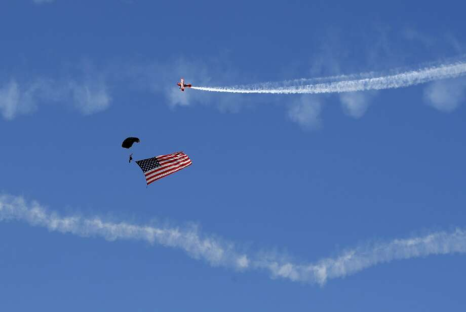 A U.S. Special Operations Command parachutist carrying an American flag is circled by stunt pilots at the start of the Great State of Maine Air Show on Saturday in Brunswick, Maine. Photo: Robert F. Bukaty, Associated Press