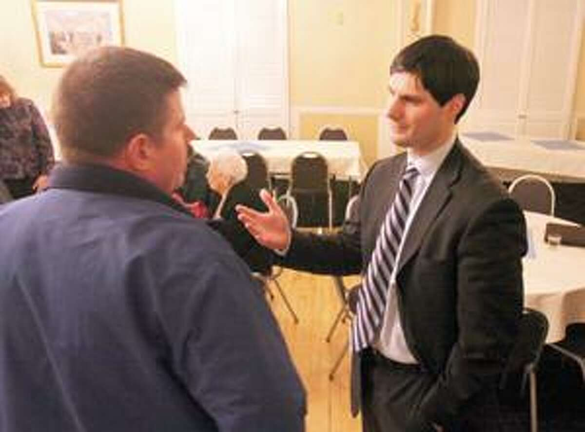 Justin Bernier, Republican running for congress in the fifth district, right, talks with David Ressel during the Republican met and greet at the Yankee Pedlar in Torrington Thursday.