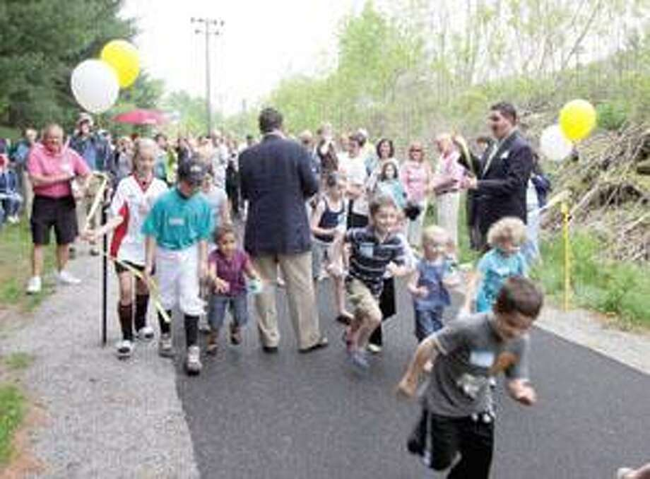 """SONJA ZINKE/Register CitizenA handful of kids make sure they are the first ones through the ribbon cut by Paul Grossman and Torrington Mayor Ryan Bingham Saturday for the dedication of the Sue Grossman Greenway in Torrington. Purchase a glossy print of this photo and more at <a href=""""http://ww.registercitizen.com"""">ww.registercitizen.com</a>"""