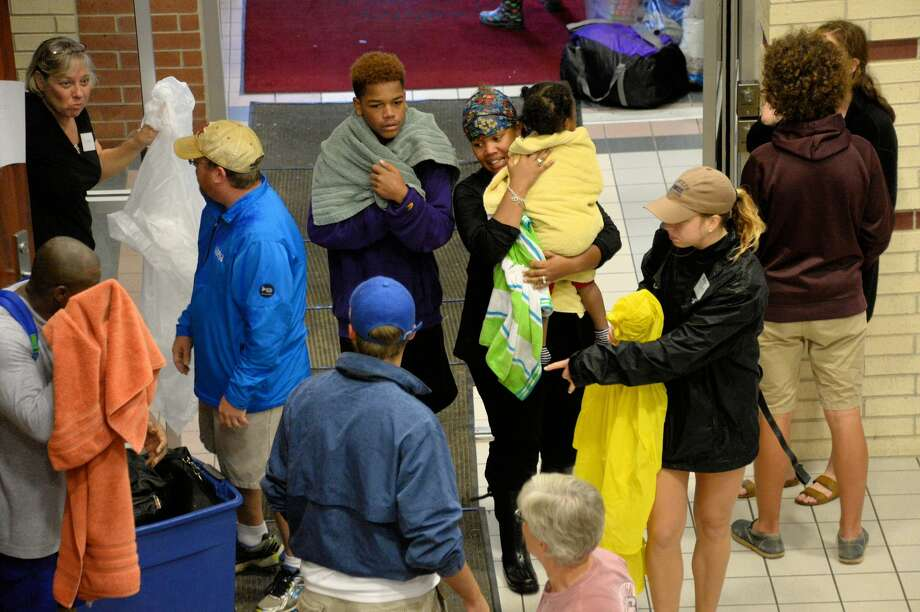 Hurricane Harvey victims are assisted by volunteers upon arrival at the Katy ISD shelter at Cinco Ranch High School in Katy, TX on August 28, 2017. Photo: Craig Moseley/Chronicle