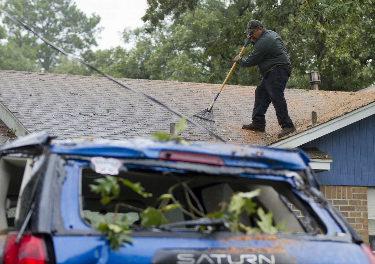 A contract worker clears the debris off the roof off Michael Heath's home after three trees fell over night damaging his roof and car in the Artesian subdivision, Monday, Aug. 28, 2017, in Conroe.