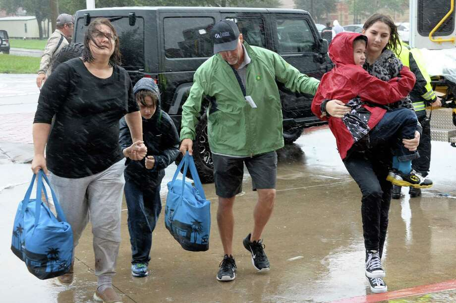 A volunteer (center) assists Hurricane Harvey victims as they arrive at the Katy ISD shelter at Cinco Ranch High School in Katy, TX on August 28, 2017. Photo: Craig Moseley, Chronicle / ©2017 Houston Chronicle