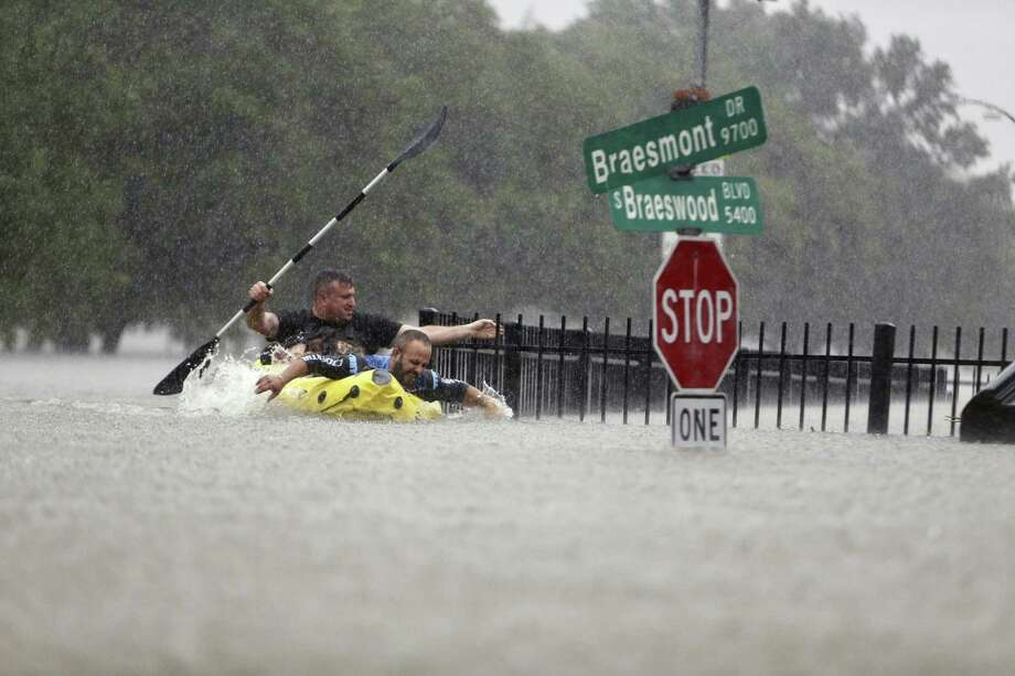 Two kayakers try to beat the current pushing them down an overflowing bayou in Houston Sunday. Remnants of Hurricane Harvey climbed high enough to begin filling second-story homes, and authorities urged stranded families to seek refuge on their rooftops. Photo: Mark Mulligan / Houston Chronicle / Internal