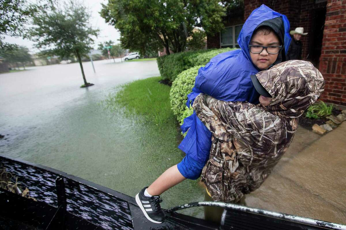 Jacob Velasco is evacuated by boat through floodwaters the Grand Mission subdivision, as the water rises from heavy rains from Tropical Storm Harvey, on Monday, Aug. 28, 2017, unincorporated Fort Bend County, Texas.