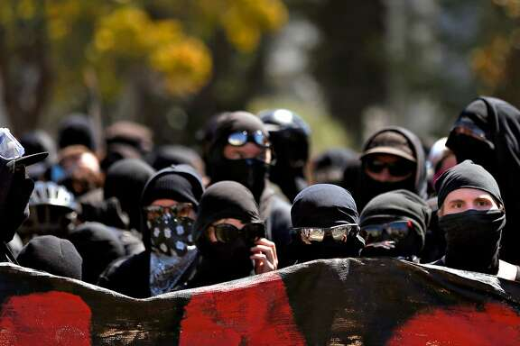 Dozens of masked anarchists stand together after the police left Dr. Martin Luther King Jr. Civic Center park after they arrived with a large group of anti-racist protesters in response to an expected far-right rally that was supposed to be held in the park August 27, 2017 in Berkeley Calif.