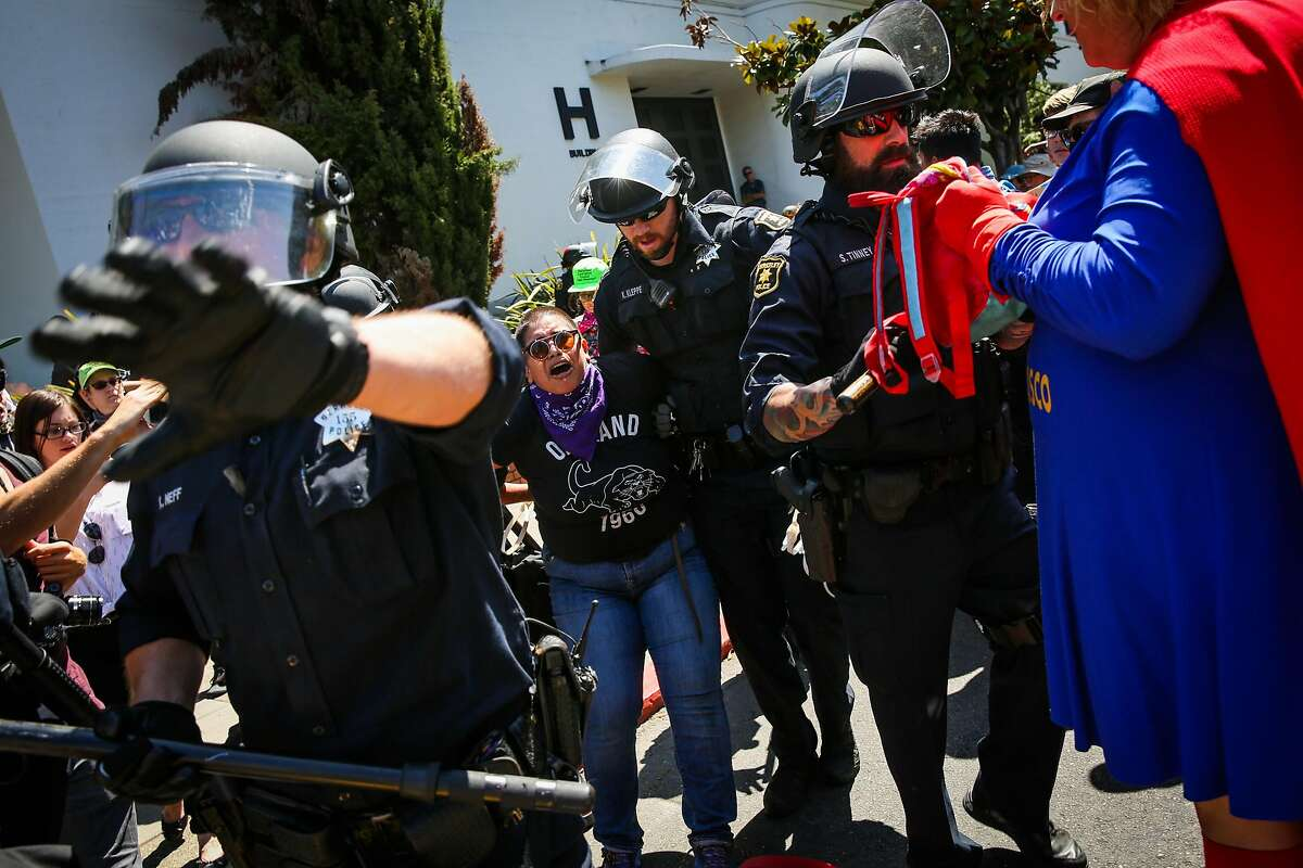 A woman is arrested on the corner of Martin Luther King Jr. Way and Allston Way during a clash between protesters in Berkeley, Calif., on Sunday, August 27th, 2017.