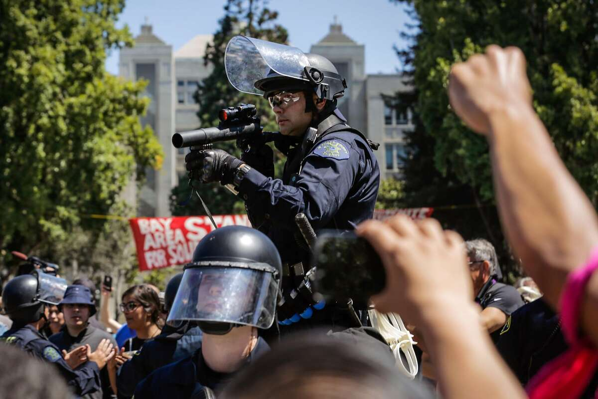 A police officer holds up a tear gas gun at a group of anti-fascist protesters at the corner of Martin Luther King Jr. Way and Allston Way during a clash between protesters in Berkeley, Calif., on Sunday, August 27th, 2017.