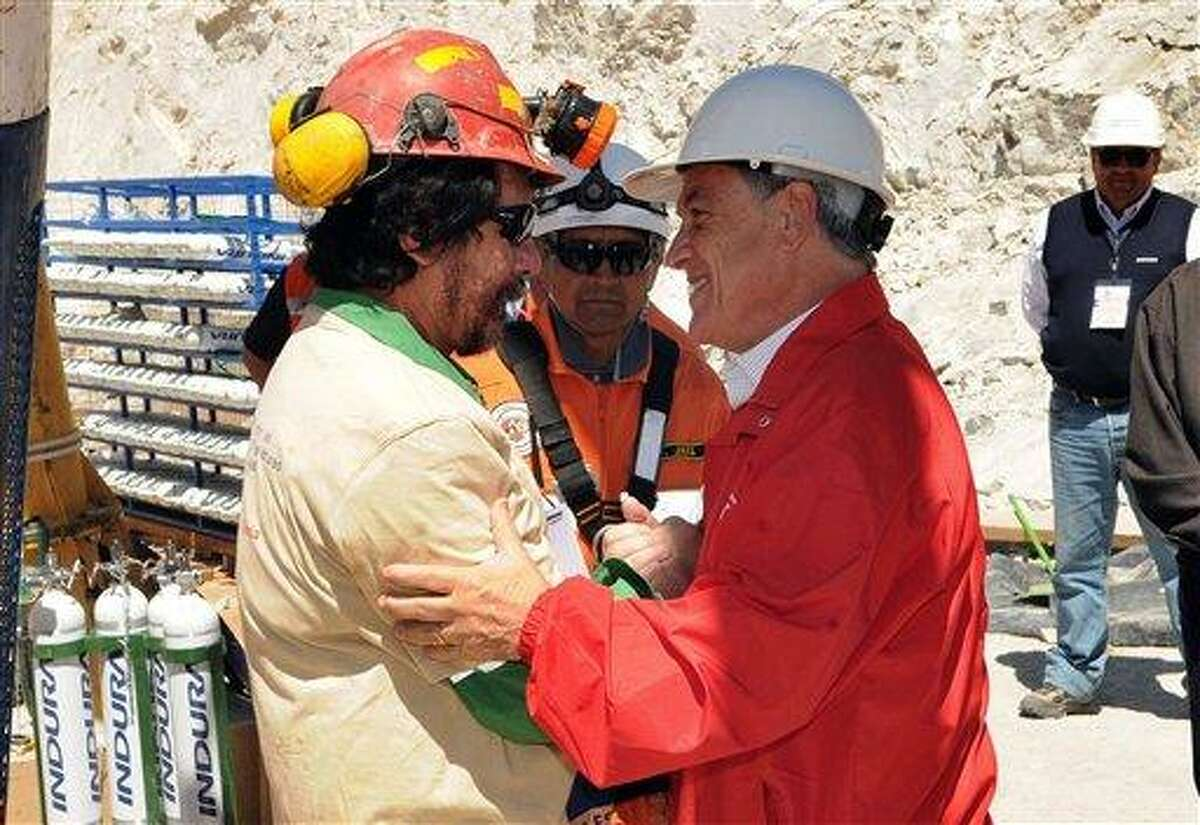 In this photo released by the Chilean Presidential Press Office, Chile's President Sebastian Pinera, back, greets miner Victor Segovia Rojas after his rescue operation from the collapsed San Jose gold and copper mine, near Copiapo, Chile, Wednesday, Oct. 13, 2010. (AP Photo/Jose Manuel de la Maza, Chilean Presidential Press Office)