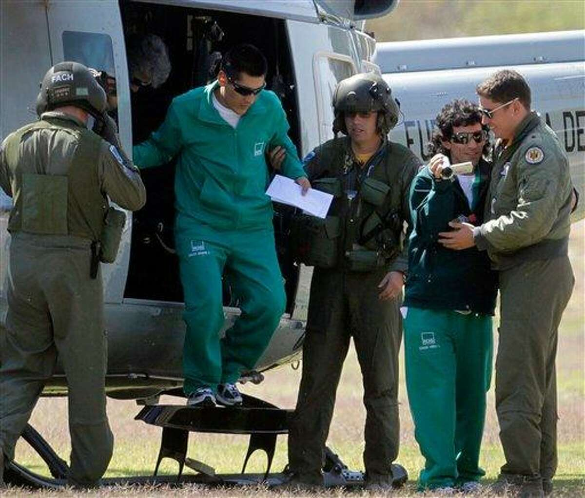 Rescued miners Claudio Yanez, second right, and Carlos Mamani Solis, second left, are helped by the crew of a Chilean Air Force helicopter upon their arrival to an Army airfield near a hospital in Copiapo after being rescued from the collapsed San Jose gold and copper mine in Chile, Wednesday, Oct. 13, 2010. (AP Photo/La Tercera, Mario Davila)