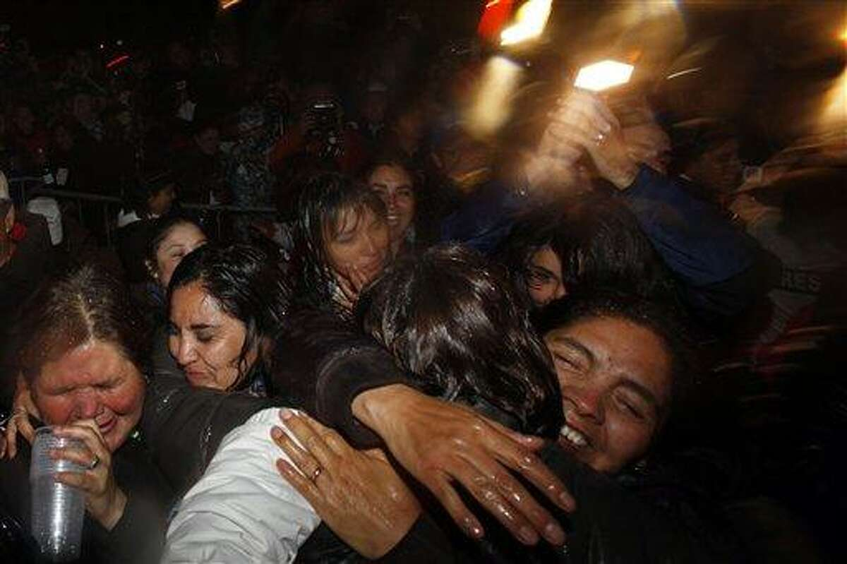 Relatives and friends of 33 freed miners celebrate the end of the successful rescue operation at the camp outside the San Jose mine near Copiapo, Chile, Wednesday Oct. 13, 2010. The 69-day underground ordeal reached its end Wednesday night after 33 trapped miners were hauled up in a cage through a narrow hole drilled through 2,000 feet of rock. (AP Photo/Natacha Pisarenko)