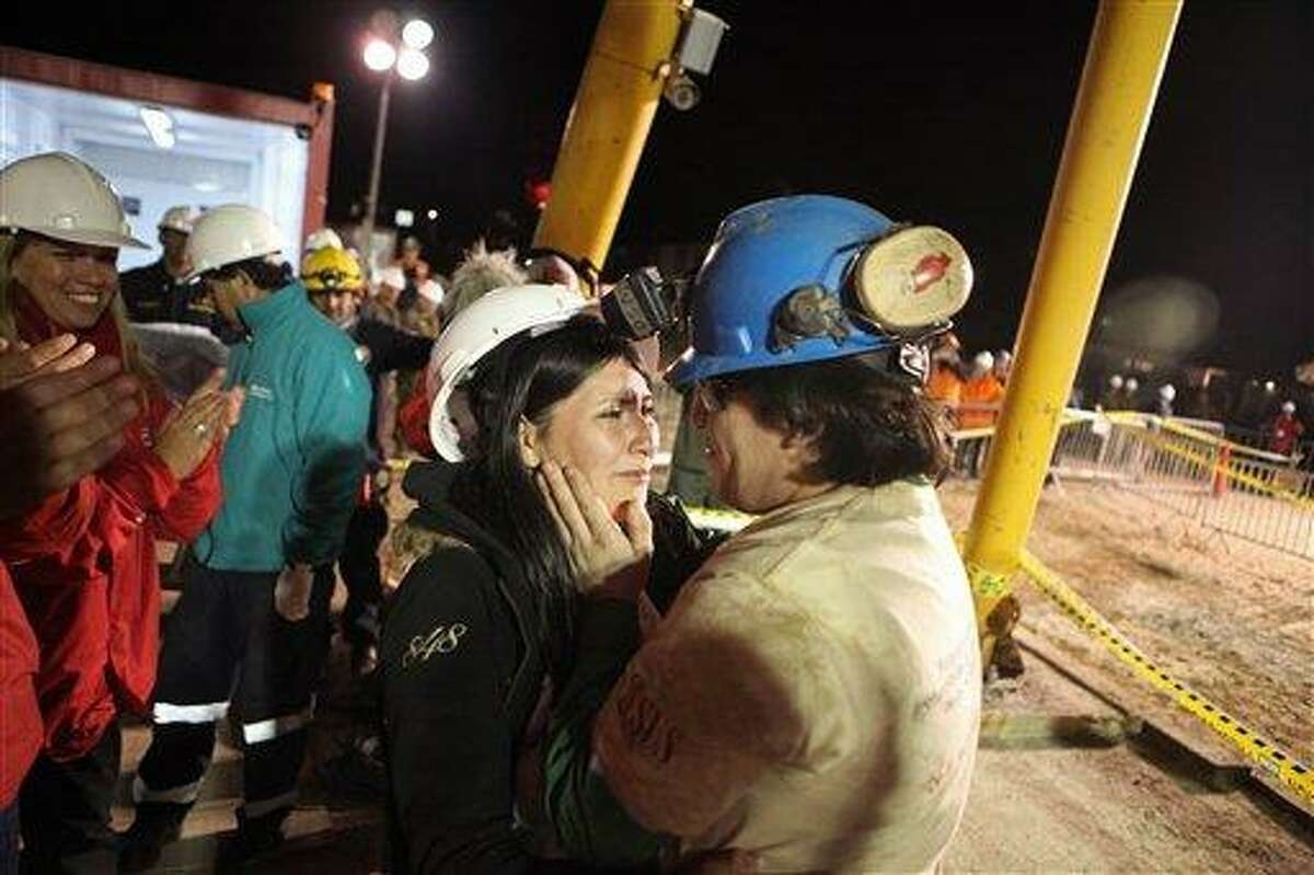 In this photo released by the Chilean government, miner Osman Araya, right, greets a relative moments after being rescued from the collapsed San Jose gold and copper mine where he had been trapped with 32 other miners for over two months near Copiapo, Chile, early Wednesday Oct. 13, 2010. (AP Photo/Hugo Infante, Chilean government)