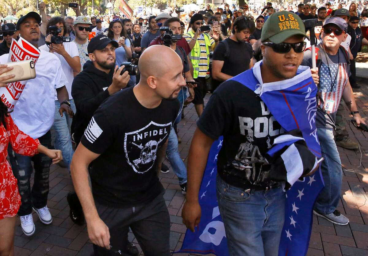 Three conservative rally attendees are pursued by a large, angry crowd of protesters on August 27, 2017 in Berkeley.