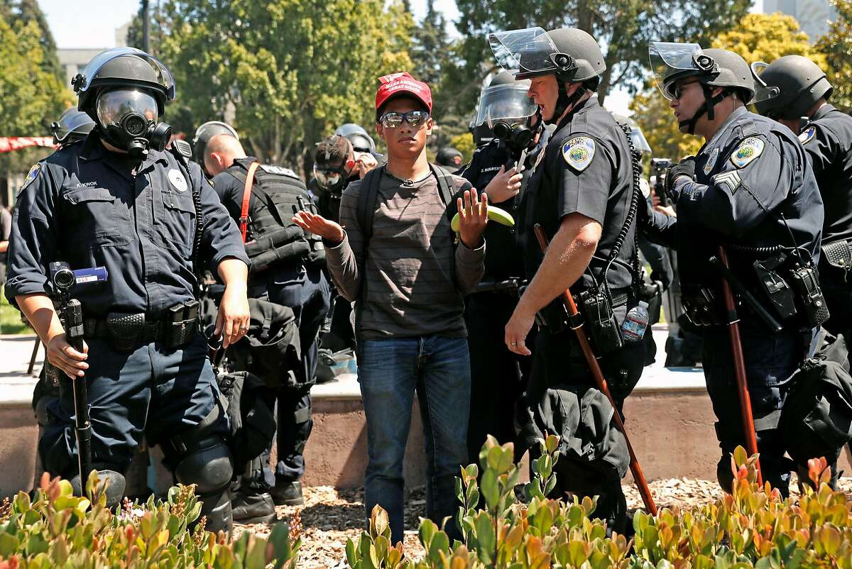 A Donald Trump supporter taunts counter protesters on the other side of a barrier while standing among Berkeley police officers on August 27, 2017.