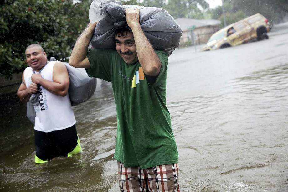 Melrose Park residents make their way down a flooded street in Houston as Tropical Storm Harvey makes its way through the area on Monday, Aug. 28, 2017. (Elizabeth Conley/Houston Chronicle via AP) / ' 2017 Houston Chronicle