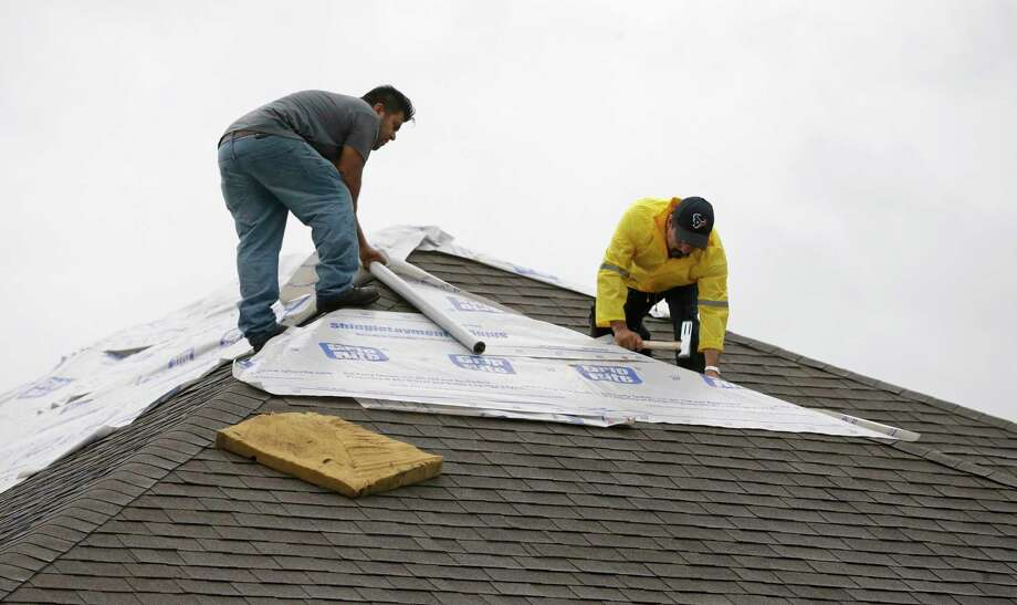 Roofers work to cover the damaged roof of a home after a tornado hit in the Lone Oak subdivision Saturday, Aug. 26, 2017, in Cypress. Several tornadoes from Hurricane Harvey have been reported. ( Melissa Phillip / Houston Chronicle ) Photo: Melissa Phillip, Staff / © 2017 Houston Chronicle