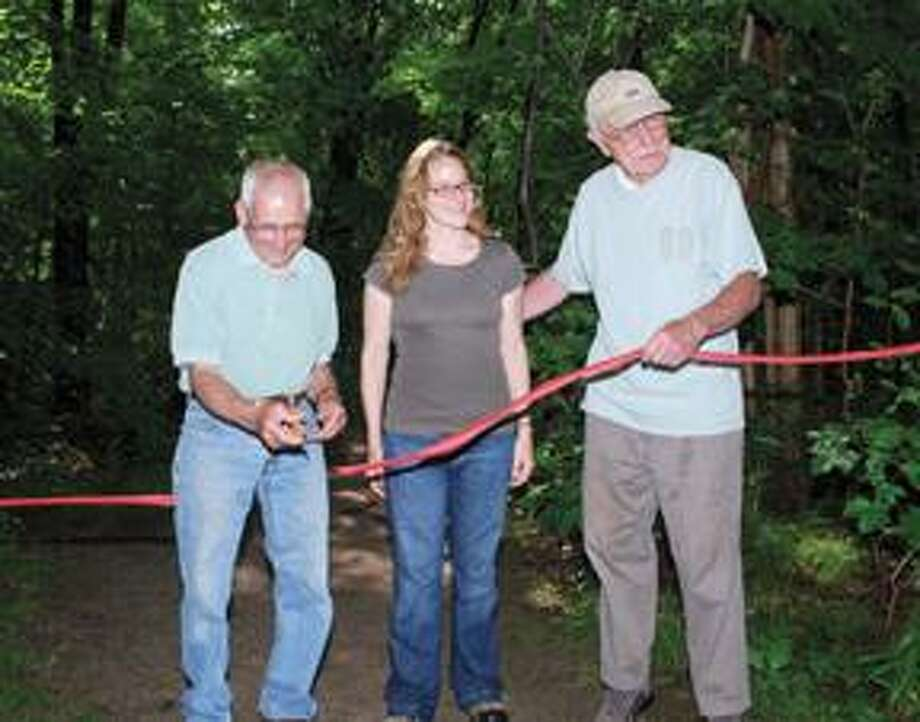 RONALD DeROSAFirst Selectman Frank Chiaramonte, left, cuts the ribbon that dedicates the town of Harwinton's new acquisition of the 65 acres of the Carros Property, which will remain a preserve. Standing in the middle is Lisa Bassani, project manager, and to the right is Hert Etter, chairman of the town's Open Space Committee.