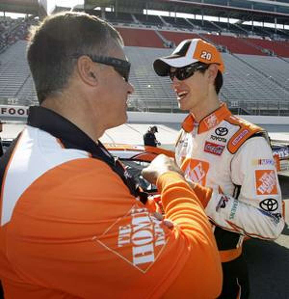 Joey Logano, right, is congratulated by a crew member after qualifying for the NASCAR Sprint Cup series Food City 500 auto race at Bristol Motor Speedway in Bristol, Tenn., Friday, March 19, 2010. Logano won the pole position for the race with a speed of 124.630 mph. (AP Photo/Chuck Burton)