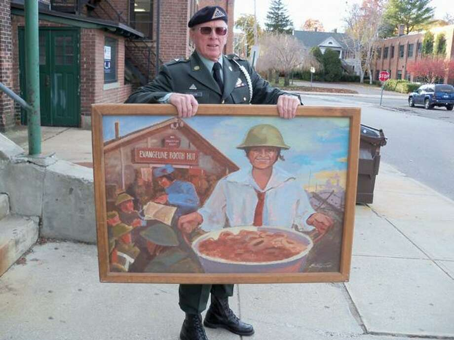 Dick Allen holds a painting of the Salvation Army handing out doughnuts to troops, which will be donated to the nearby military museum.