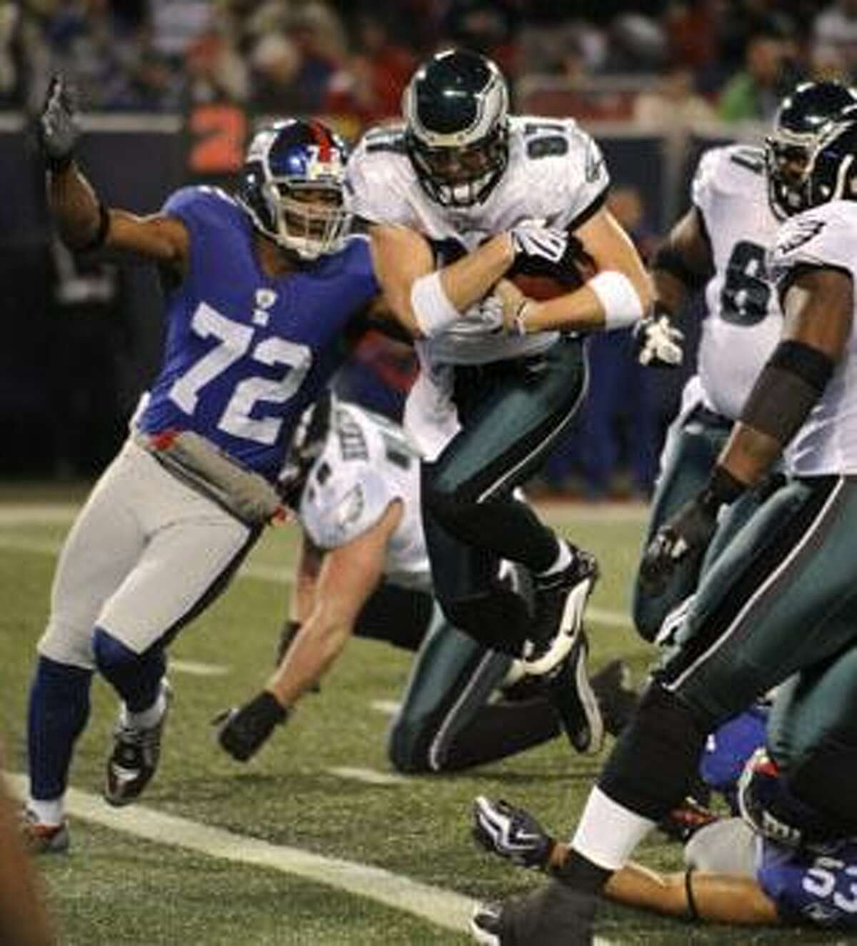 Philadelphia Eagles tight end Brent Celek (87) crosses the goal line to score a touchdown as New York Giants defensive end Osi Umenyiora (72) comes in late for the play Dec. 13 in East Rutherford, N.J.