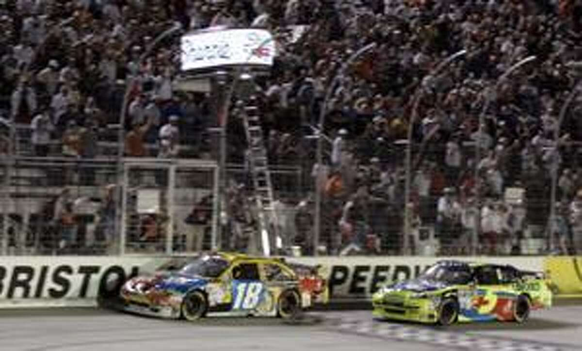 AP Kyle Busch (18) crosses the finish line ahead of Mark Martin (5) to win the Sharpie 500 in Bristol, Tenn., Saturday.