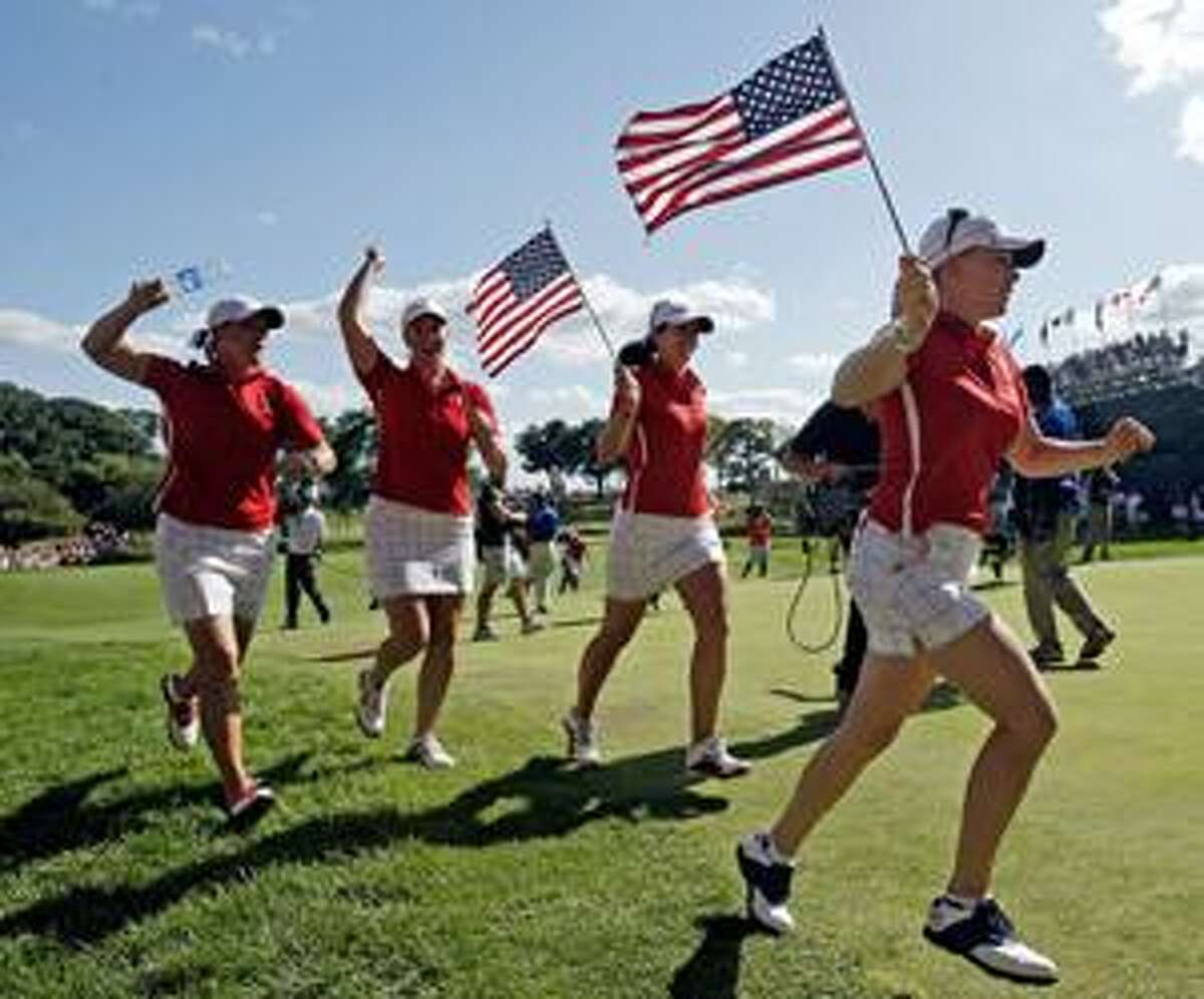 AP Team USA's Kristy McPherson, left to right, Brittany Lincicome, Nicole Castrale and Morgan Pressel celebrate after their singles matches at the Solheim Cup golf tournament Sunday at Rich Harvest Farms in Sugar Grove, Ill. The USA team won 16-12 to retain the cup.