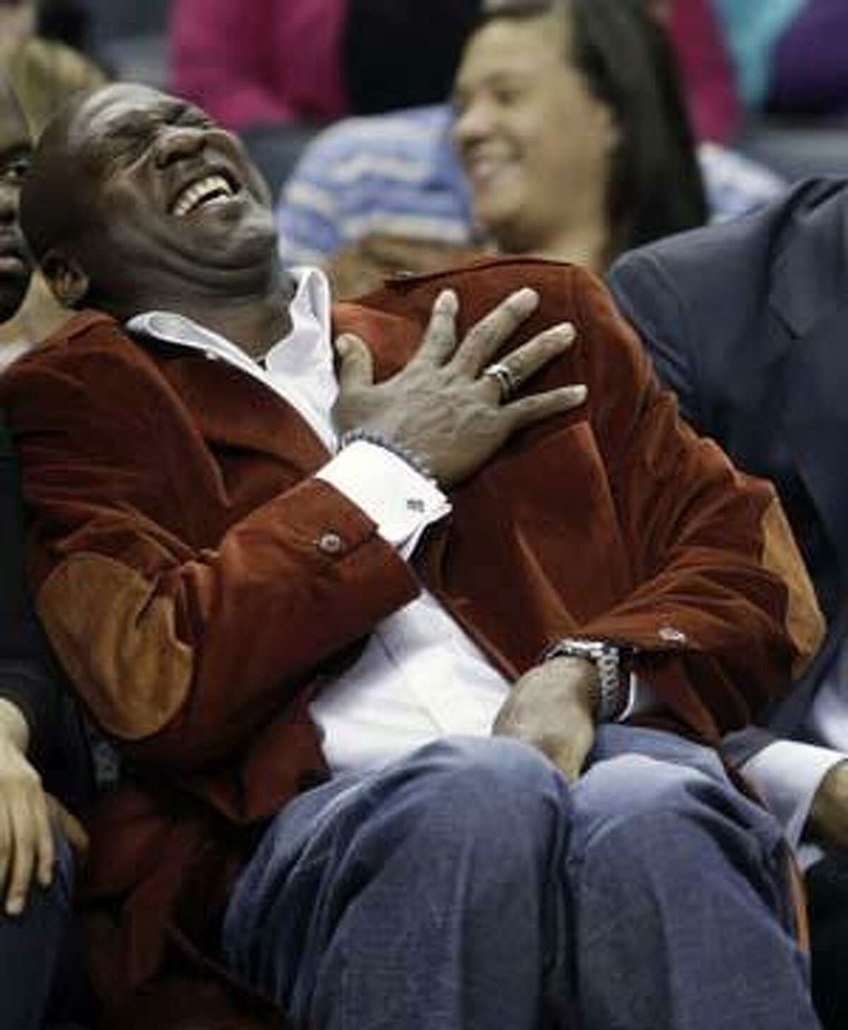 Michael Jordan laughs in the first half of the Charlotte Bobcats' NBA basketball game against the Dallas Mavericks in Charlotte, N.C., Monday, March 1, 2010. Jordan has agreed to buy controlling interest in the Bobcats. (AP Photo/Chuck Burton)