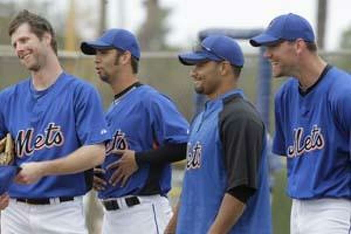 New York Mets pitcher Nelson Figueroa, second from left, jokes with fellow pitcher John Maine, left, as teammates Johan Santana, second from right, and Mike Pelfrey, right, laugh nearby during spring training baseball Saturday, Feb. 27, 2010, in Port St. Lucie, Fla. (AP Photo/Jeff Roberson)