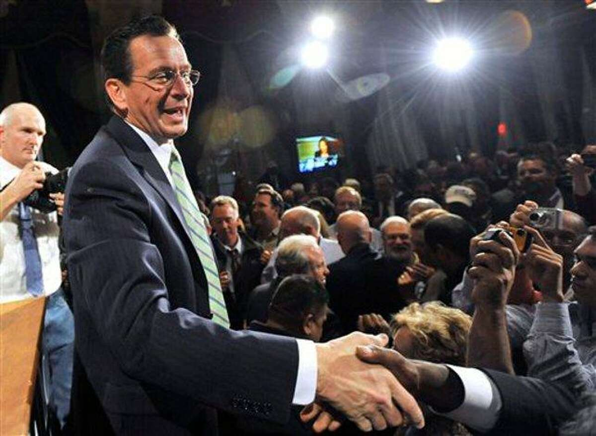 Democratic candidate for governor Dan Malloy shakes hands with supporters in Hartford, Conn., early Wednesday, Nov. 3, 2010. (AP Photo/Jessica Hill)