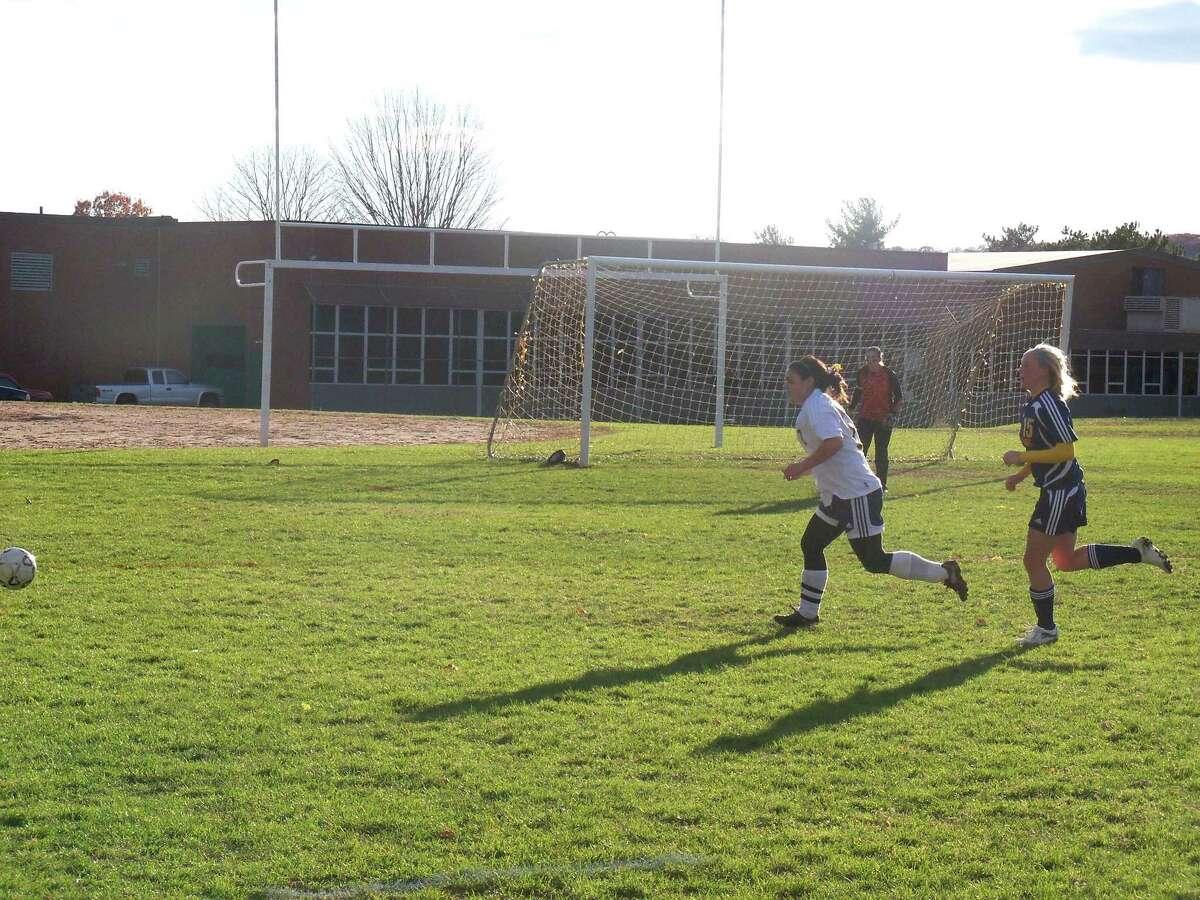 KEVIN D. ROBERTS/Register Citizen Wolcott Tech's Shaun Zbell, left, and Gilbert's Meghan Dzielak, right, chase after the ball during Monday afternoon's soccer match at Wolcott Tech in Torrington. The Yellowjackets won 4-1.