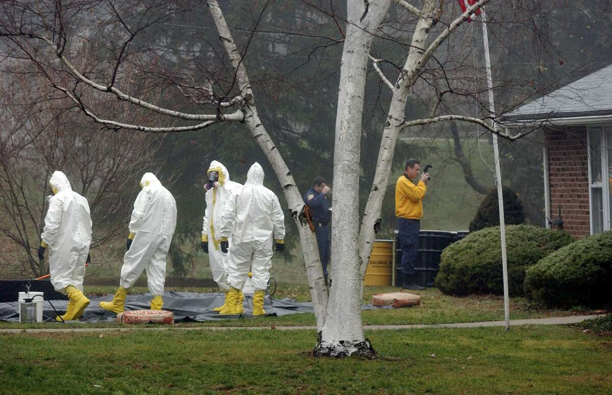In this Nov. 30, 2001 file photo, a decontamination crew dressed in hazmat suits stands together as an investigator takes photographs outside Ottilie Lundgren's home in Oxford, Conn., after the house was declared a crime scene. It was ruled that Lundgren, 94, died of inhalation anthrax on Nov. 21. (AP Photo/Steve Miller, File)