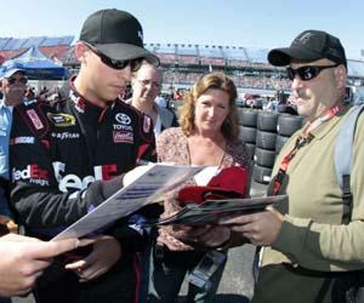 In this Saturday, Oct. 30, 2010 photo, Driver Denny Hamlin signs autographs after he made his qualifying run in the AMP Energy Juice 500 auto race at the Talladega Superspeedway, in Talladega, Ala. (AP Photo/John Bazemore)