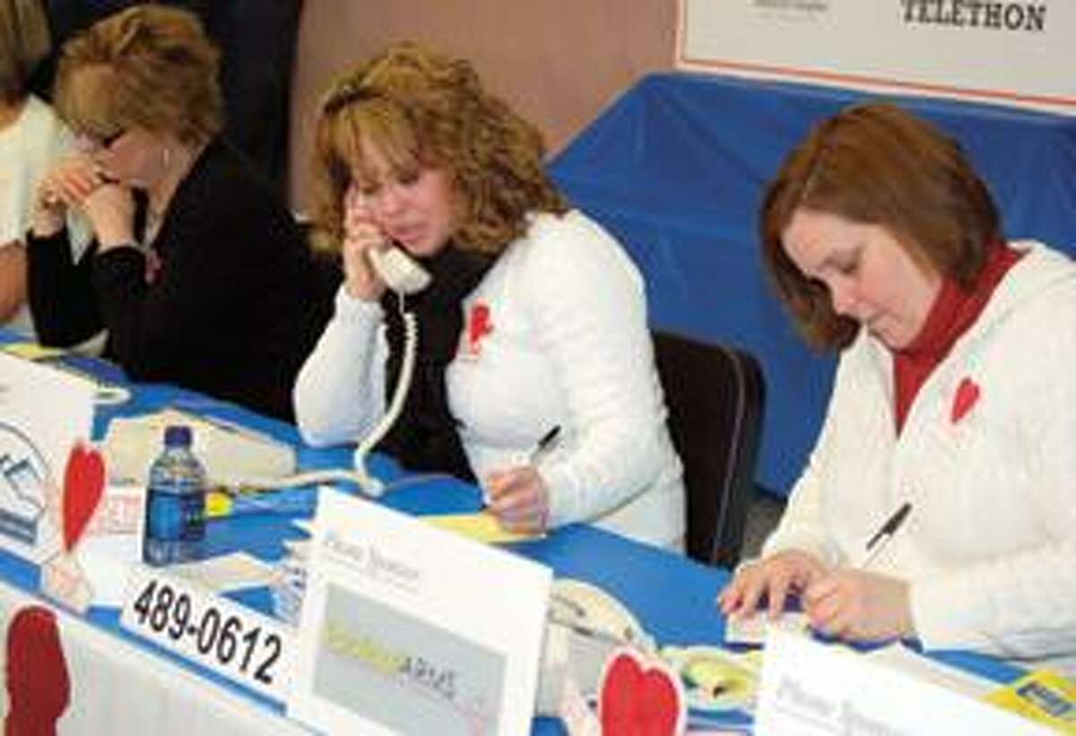 RONALD DEROSA/Register CitizenLitchfield Center School volunteers Heather Todor, center, and Michele Kaplan, right, answer phones and write down donation pledges from callers during the St. Jude's Telethon held on Sunday.