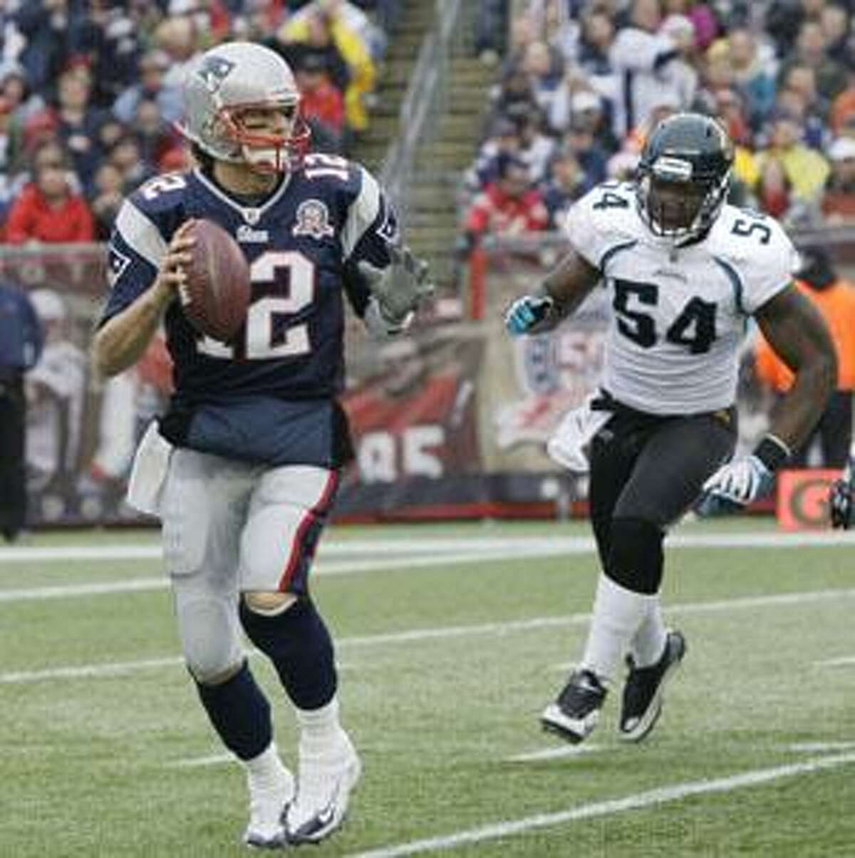 New England Patriots quarterback Tom Brady (12) looks for a receiver as Jacksonville Jaguars defensive end Quentin Groves (54) closes in during the first half Sunday in Foxboro, Mass.