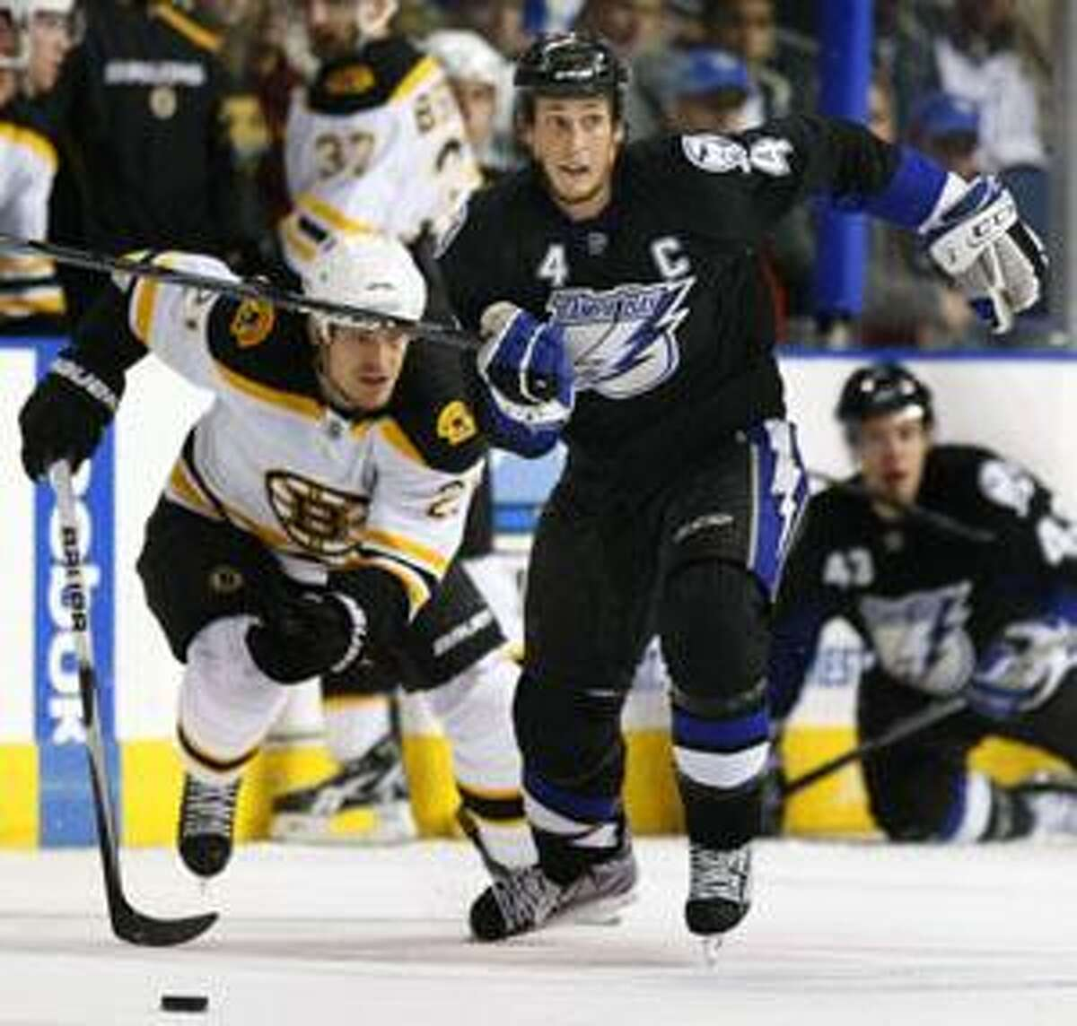 Tampa Bay Lightning center Vincent Lecavalier (4) outskates Boston Bruins defensmen Andrew Ference (21) to the puck during the second period Monday in Tampa, Fla. The Lightning defeated the Bruins 2-1.