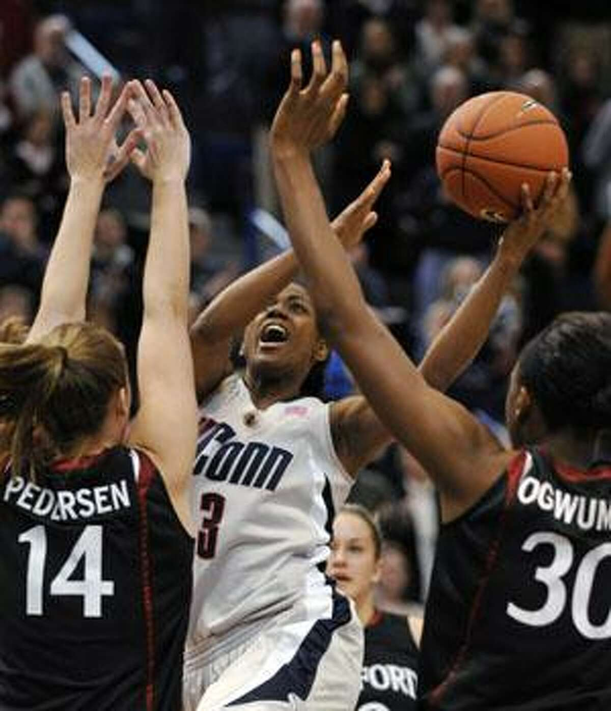 Connecticut's Tiffany Hayes splits the defense of Stanford's Kayla Pedersen (left) and Nnemkadi Ogwumike (right) during the first half on Dec. 23 in Hartford.