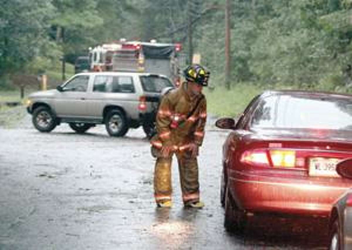 SONJA ZINKE/Register CitizenHarwinton Westside Volunteer Firefighter, Aaron Franzi mans a road block on South Road in Harwinton Friday evening. Numerous downed trees closed many roads in Harwinton after Friday's storm. Purchase a glossy print of this photo and more at www.registercitizen.com