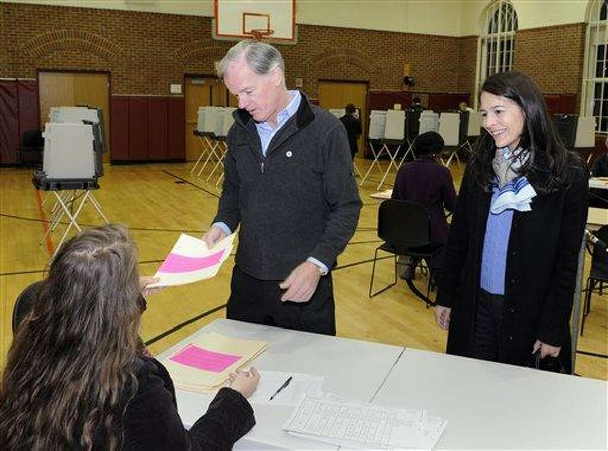 Connecticut Republican gubernatorial candidate Tom Foley takes a ballot before voting as his wife Leslie Fahrenkopf Foley looks on in Greenwich, Conn., on Tuesday, Nov. 2, 2010. (AP Photo/Fred Beckham)
