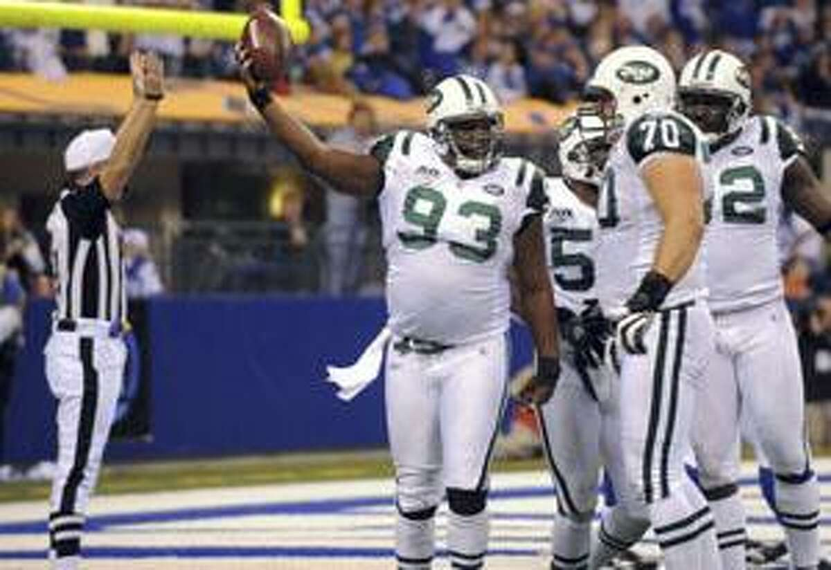 New York Jets defensive end Marques Douglas celebrates with teammates Mike Devito (70) and Shaun Ellis, right, after he recovered a fumble by Indianapolis Colts backup quarterback Curtis Painter for a touchdown during the third quarter Sunday in Indianapolis. The Jets won 29-15.