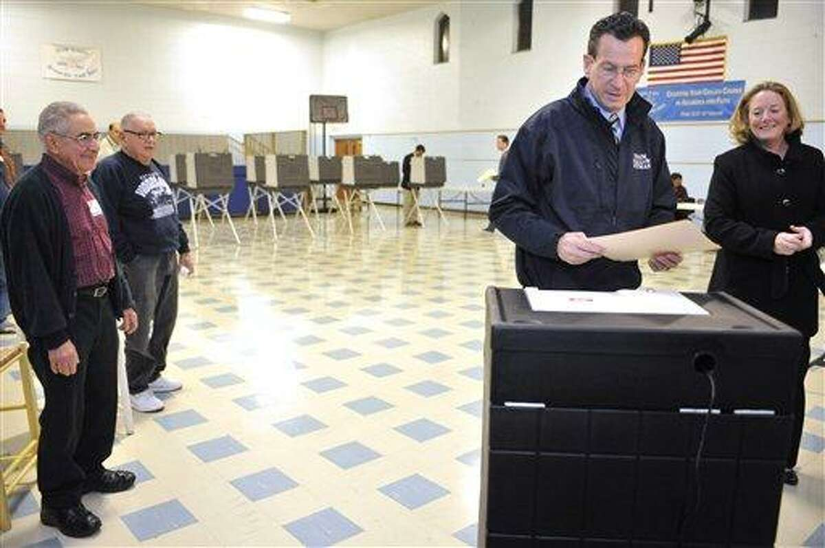 Democratic candidate for governor Dan Malloy votes, as wife Cathy, right, and volunteers look on, in Stamford, Conn., Tuesday, Nov. 2, 2010. (AP Photo/Jessica Hill)