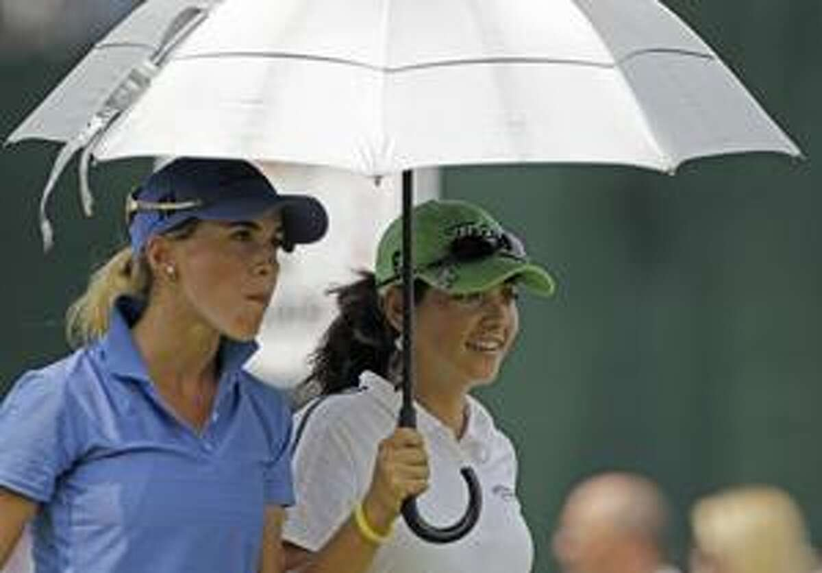 AP Belen Mozo, left, of Spain, and Azahara Munoz of Spain walk under an umbrella during their practice round for the U.S. Women's Open golf tournament at Oakmont Country Club in Oakmont, Pa., Tuesday. Temperatures could be a problem at the tournament as a heat wave envelops the Northeast.