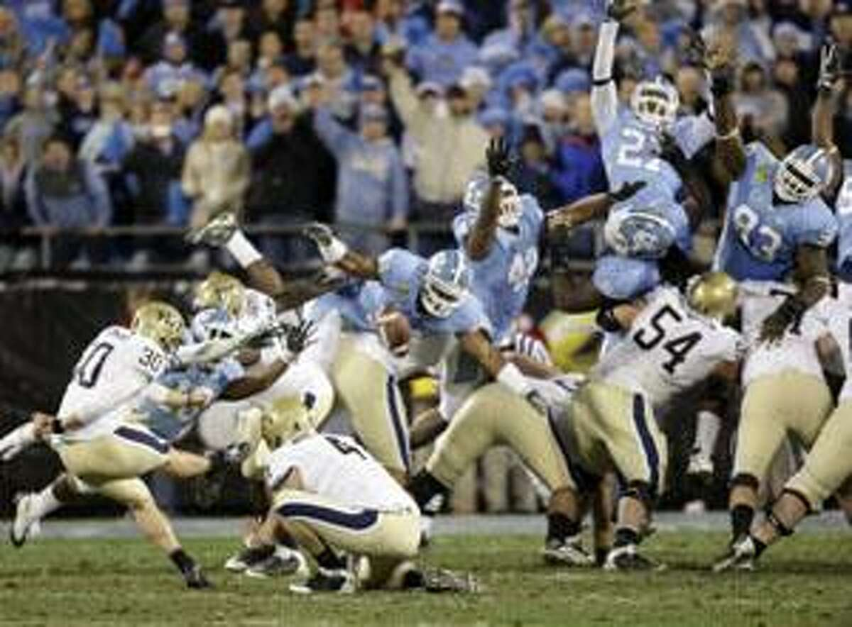 AP Pittsburgh kicker Dan Hutchins (30) kicks the winning field goal as North Carolina players try for the block in the final seconds of Pittsburgh's 19-17 win in the Meineke Bowl in Charlotte, N.C., Saturday.