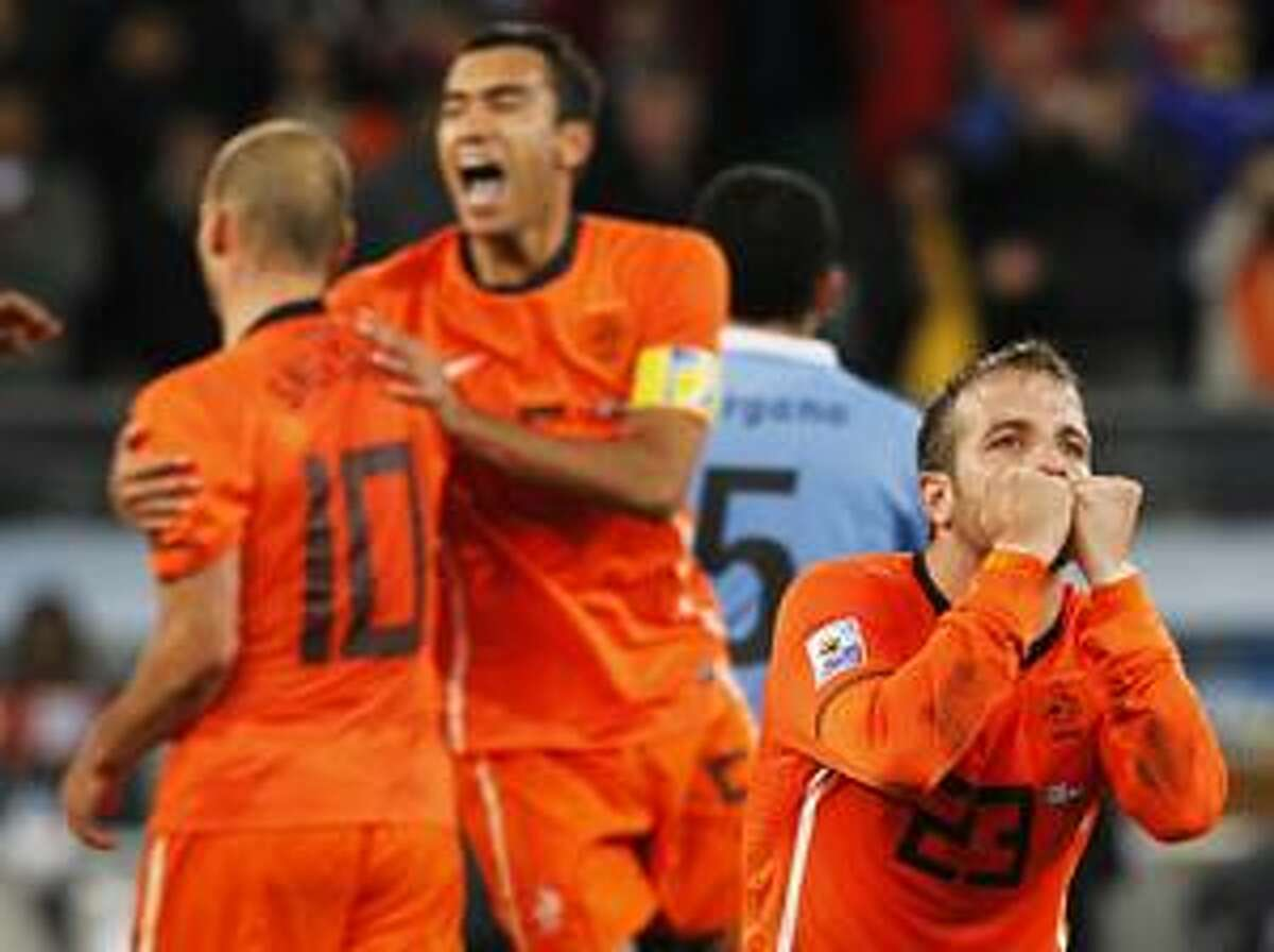 AP Netherlands player Rafael van der Vaart, front right, celebrates with Wesley Sneijder, left, and Giovanni van Bronckhorst, center, following the World Cup semifinal soccer match against Uruguay at the Green Point stadium in Cape Town, South Africa, Tuesday. Netherlands defeated Uruguay 3-2.
