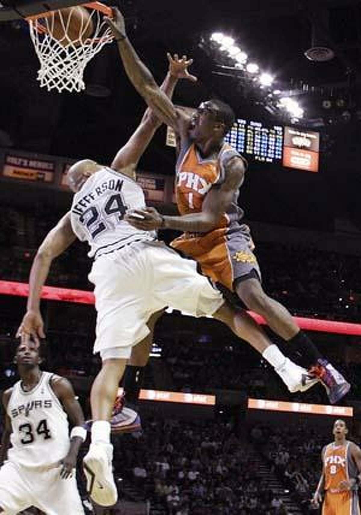 AP Phoenix Suns forward Amare Stoudemire, right, dunks over San Antonio Spurs forward Richard Jefferson during the second half of Sunday's game in San Antonio. Jefferson and the Spurs got the last laugh, however, winning the game 113-110.