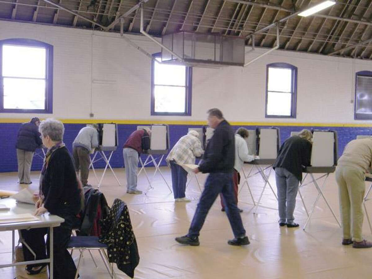 MIKE AGOGLIATI/Register Citizen Voters cast their ballots in Torrington on Tuesday.