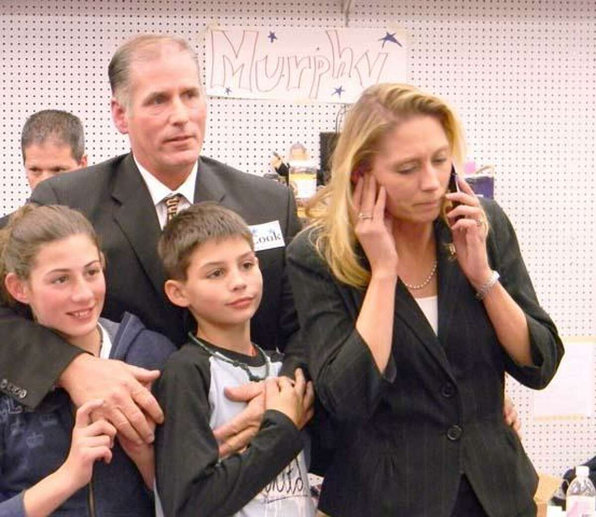 MIKE AGOGLIATI/ Register CitizenState Rep. Michelle Cook, D-65 takes a phone call after learning of her re-election. Cook's husband Chris, and children, Ashlynn and Billy stand by her side.