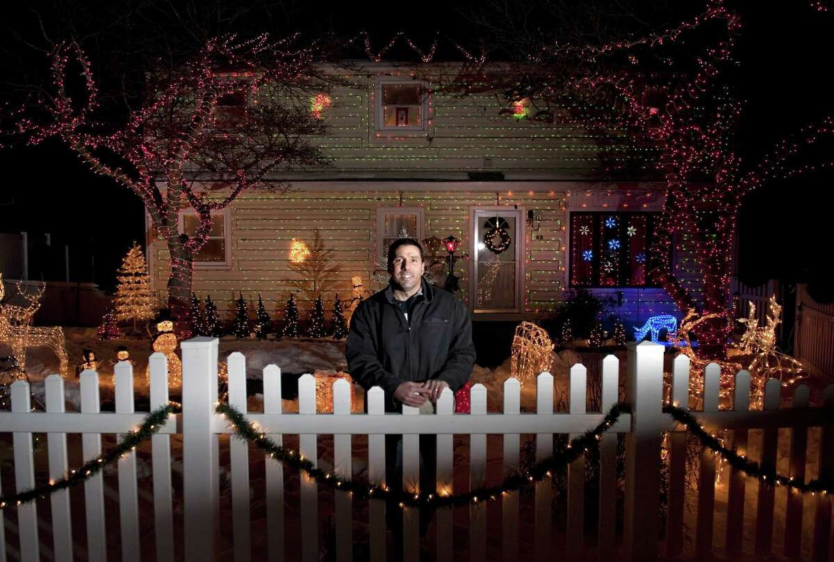 In this photo taken Tuesday Dec. 22, 2009, Tony Pampena stands in front of his decorated house in Stamford, Conn. Pampena for years has decorated his house on Lewelyn Road with tens of thousands of lights. (AP Photo/The Stamford Advocate, Douglas Healey)