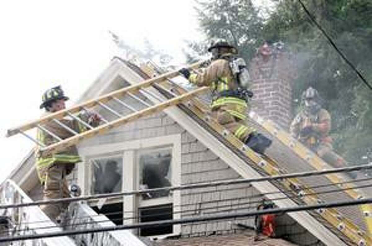 Torrington firefighter Dan Kibbe, hands the ladder to firefighter Aaron Picz as Lt. Dave Tripp gets ready to vent the roof during the Wolcott Avenue fire Thursday in Torrington.