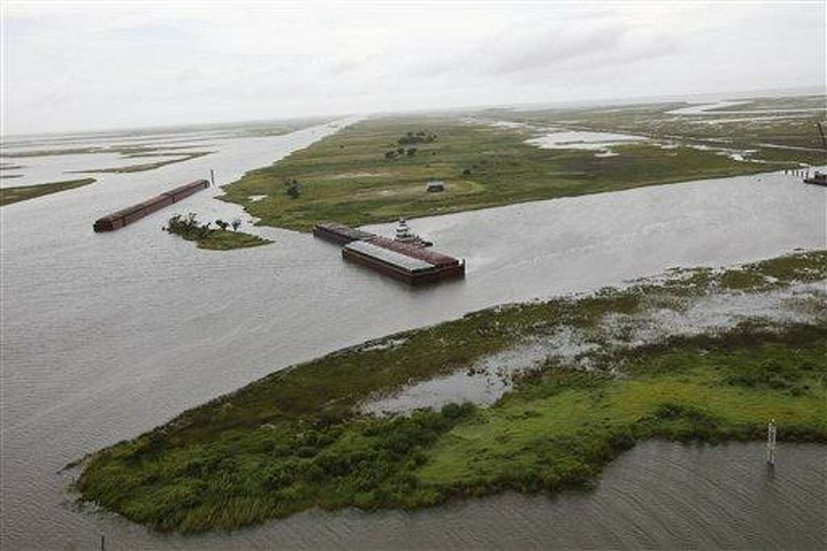 A possible oil sheen is seen as barges lined up to block oil are seen from the air in The Rigolets, which connects the Gulf of Mexico and Lake Borgne to Lake Pontchartrain, in New Orleans, La., Tuesday, July 6, 2010. Oil from the Deepwater Horizon oil spill has infiltrated Lake Pontchartrain for the first time. (AP Photo/Gerald Herbert)