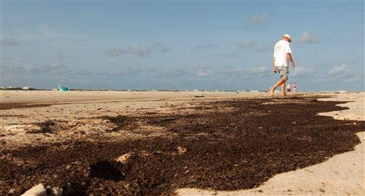 An unidentified beach walker makes his way past an ugly stain of oil on the beach in Orange Beach Ala., Wednesday, July 7, 2010. Oil washed ashore with the tide overnight, leaving a stain that brought out dozens of BP workers to clean.(AP Photo/Dave Martin)